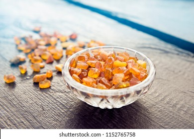 Cute little bowl cup full of small Baltic amber chips on dark brown wooden background. The Baltic region is home to the largest known deposit of amber, called Baltic amber or succinite.