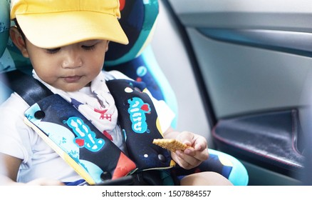 Cute little boy 1 year old toddler baby boy child to fasten belt on car seat in car before driving, happy traveling with kid concept.