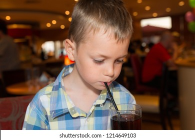A cute little boy with ADHD, Aspergers Syndrome, Autism has a drink through a straw before his meal
