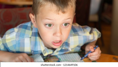 A cute little boy with ADHD, Aspergers Syndrome, Autism has fun playing and drawing with colouring crayons before his meal