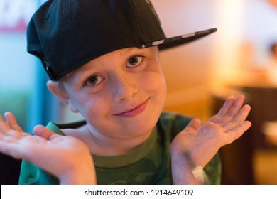 A cute little boy with ADHD, Aspergers Syndrome, Autism has fun playing around with his cap before an evening meal