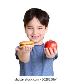 Cute little boy with apple and hamburger on white background