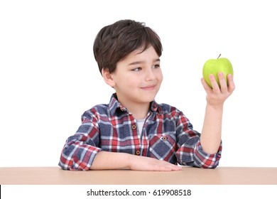 Cute little boy with apple sitting at table, on white background