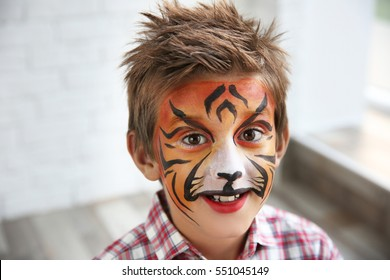 Cute little boy with aqua makeup of tiger muzzle