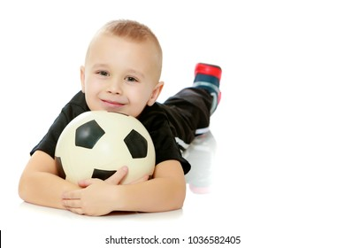 Cute little boy with the ball.The boy lying on the ground and hugs the ball with your hands.Isolated on white background.