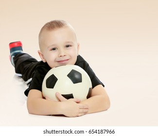 Cute little boy with the ball.The boy lying on the ground and hugs the ball with your hands.