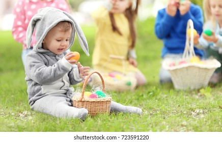 Cute little boy with basket on green grass in park. Easter egg hunt concept