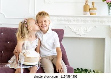 Cute little boy and beautiful girl are sitting on a chair together. Younger sister congratulates his older brother on his birthday. Holds a large white cake with sprinkled cream. Clean shirt blouse