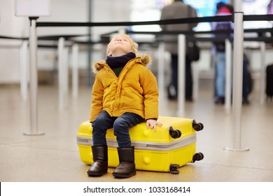 Cute little boy with big yellow suitcase at international airport before flight. Charming kid waiting boarding in terminal. Family travel with child concept