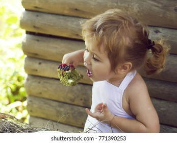 Cute little boy with blond hair ponytail in white pinafore eats fruit cake with berries on summer day on wooden background
