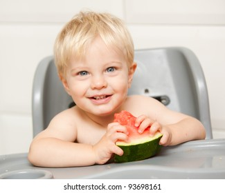 A cute little boy with blonde hair in a high chair with watermelon looking at the camera.