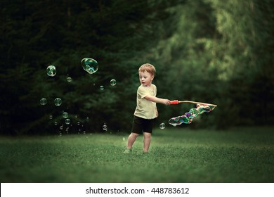 Cute little boy is blowing big bubbles. Image with selective focus and toning