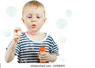 cute little boy blowing bubbles on white background