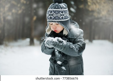 Cute little boy blowing snow flakes from his hands outdoors on a winter's day
