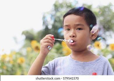 Cute little boy is blowing a soap bubbles