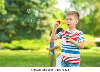 Cute little boy blowing soap bubbles outdoors