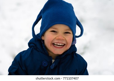 The cute little boy in blue jacket and cap is laughing at winter outdoors on white background.