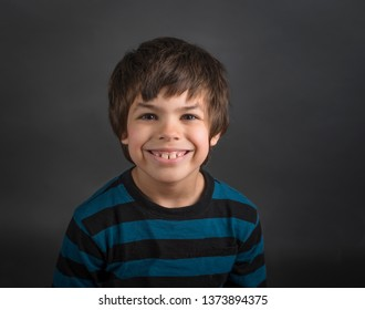 Cute little boy in blue striped shirt with goofy grin
