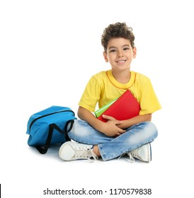 Cute little boy with books on white background