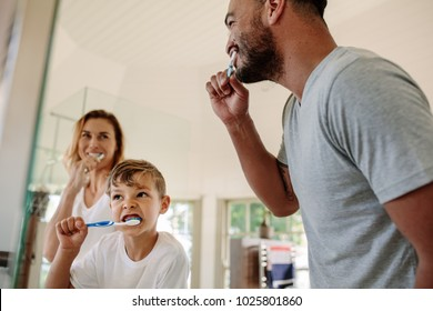 Cute little boy brushing teeth with his father and mother in bathroom. Young family brushing teeth together in bathroom.