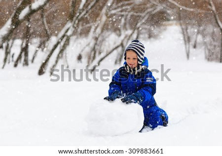 cute little boy building snowman in winter park