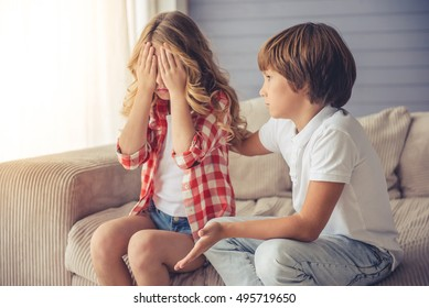 Cute little boy is calming pretty little girl while they both are sitting on sofa at home