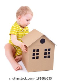Cute little boy with cardboard house isolated on white