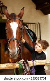 Cute little boy caressing horse.