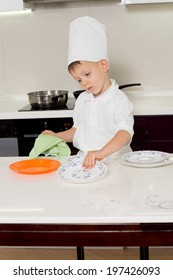 Cute little boy chef getting ready for dinner wiping and cleaning the plates before placing them on the kitchen table