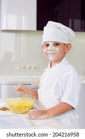 Cute little boy in a chefs uniform baking a cake in the kitchen adding ingredients from the recipe into his mixing bowl