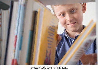 Cute little boy choose a book on the bookshelf