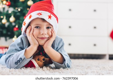 Cute little boy with Christmas hat lying on white carpet and looking at camera