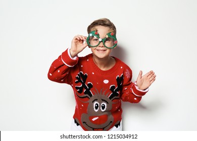 Cute little boy in Christmas sweater with party glasses on white background