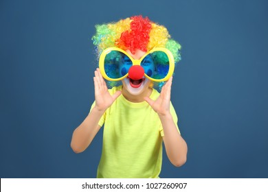 Cute little boy with clown makeup in big glasses on color background. April fool's day celebration