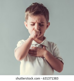 Cute little boy is coughing, on gray background