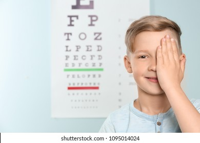 Cute little boy covering eye in ophthalmologist office