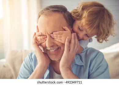 Cute little boy is covering his grandpa's eyes and smiling while playing with him at home