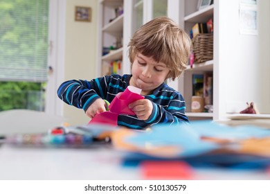 Cute little boy cutting shapes out of colored paper. Children being creative, developing imagination, creativity, do it yourself concept
