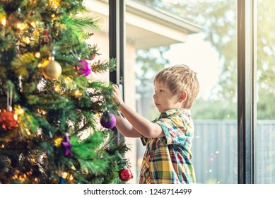 Cute little boy  decorating a Christmas tree in South Australia