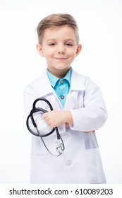 Cute little boy doctor holding stethoscope and smiling at camera  isolated on white