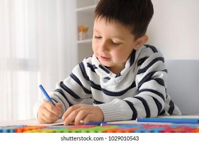 Cute little boy doing homework indoors