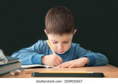 Cute little boy doing homework against black background