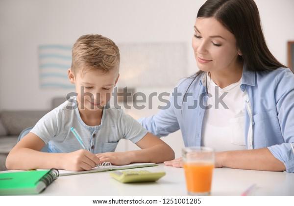 Cute little boy doing homework with mother