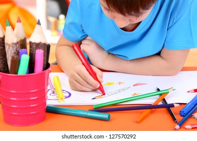 Cute little boy drawing in his notebook