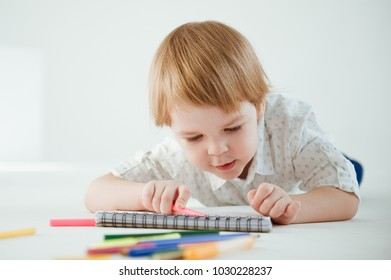 Cute little boy is drawing with markers on the floor in a bright room.