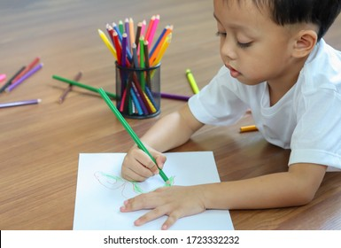 Cute little boy drawing a monster with color pencils. Creativity concept.
