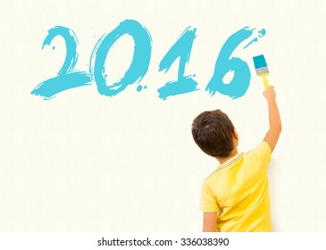 Cute little boy drawing new year 2016 with painting brush on wall background