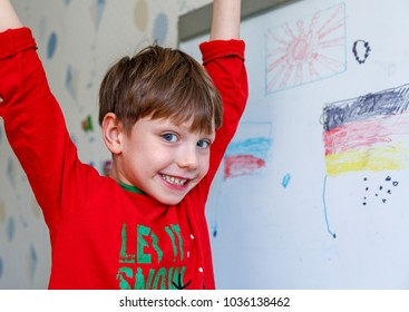 Cute little boy drawing on white board with felt pen and smiling. Early education concept