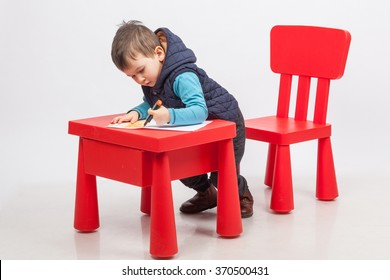 Cute little boy drawing, red table and chair, on white background. Childhood education concept