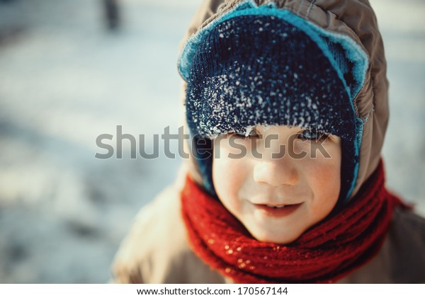 Cute little boy dressed in winter clothes with snow on his cap